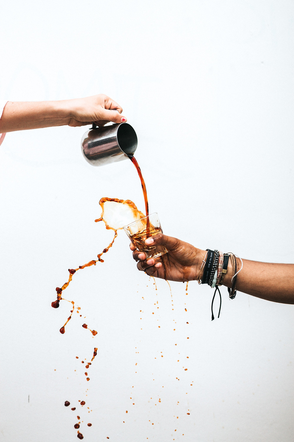 A person pouring coffee into a cup.