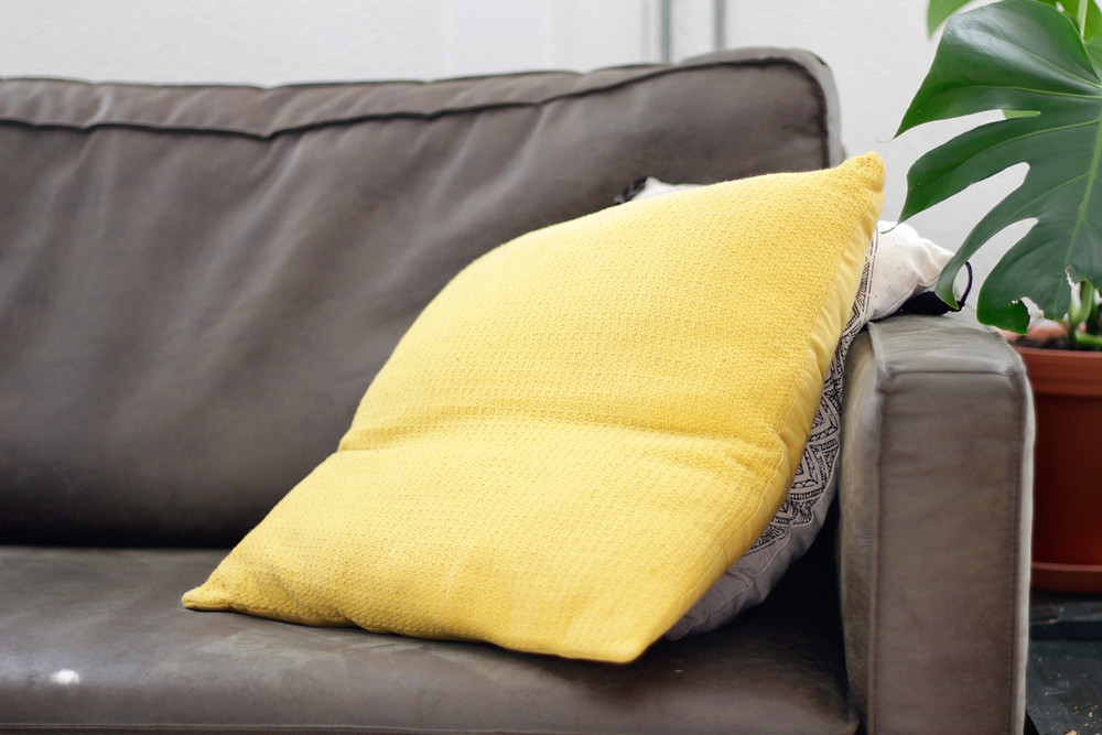 Grey couch with yellow pillow