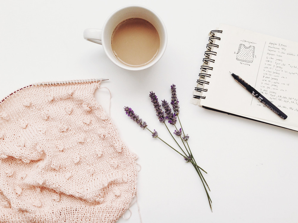 Pink bobble knitting on the needles, sprigs of lavender, a cup of coffee, and a notebook with vest schematic sketch drawn in it