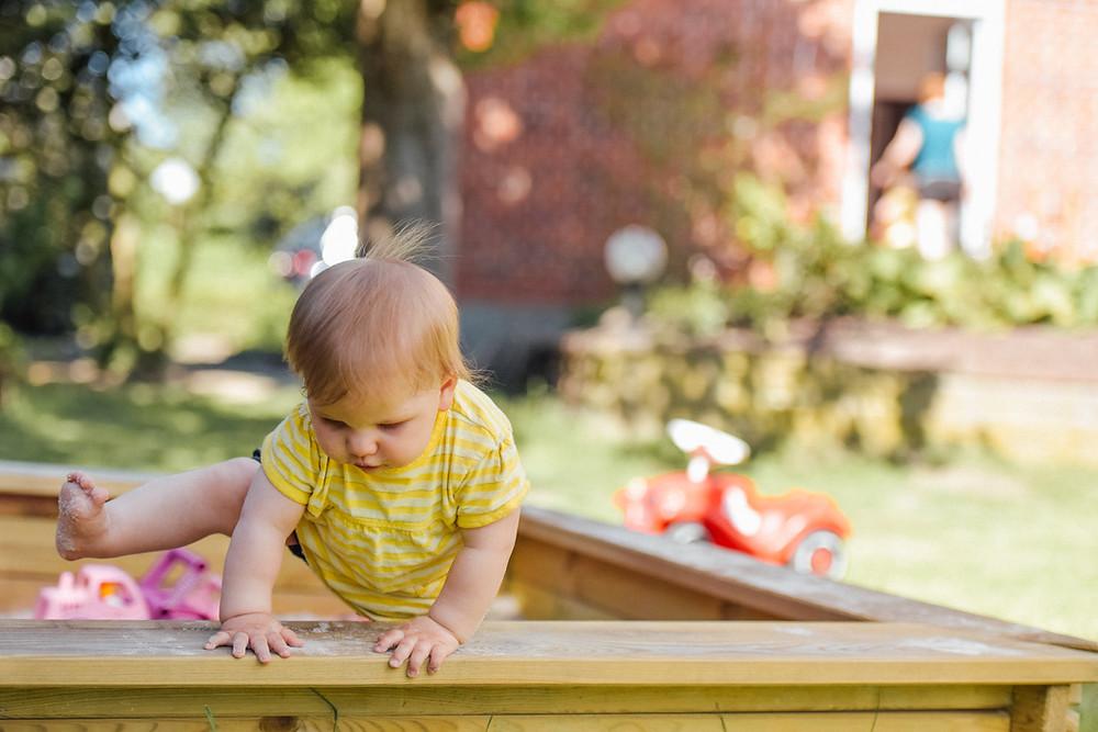 toddler climbing out of a sandbox
