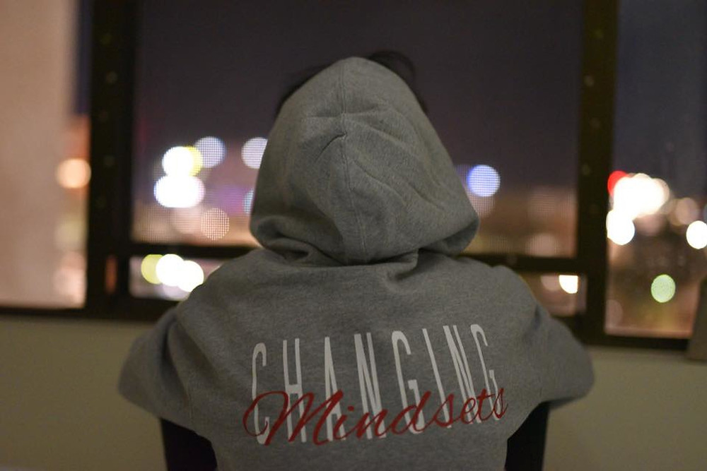 Image of the back of a person wearing a hoody with the words Changing Mindsets written across the back