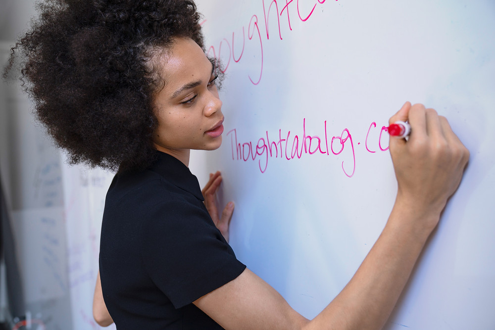African lady writing on whiteboard