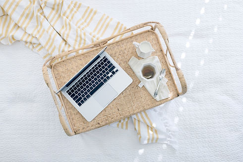 Laptop, teacup, milk, spoon and napkin on rattan tray with beige and white blanket in background