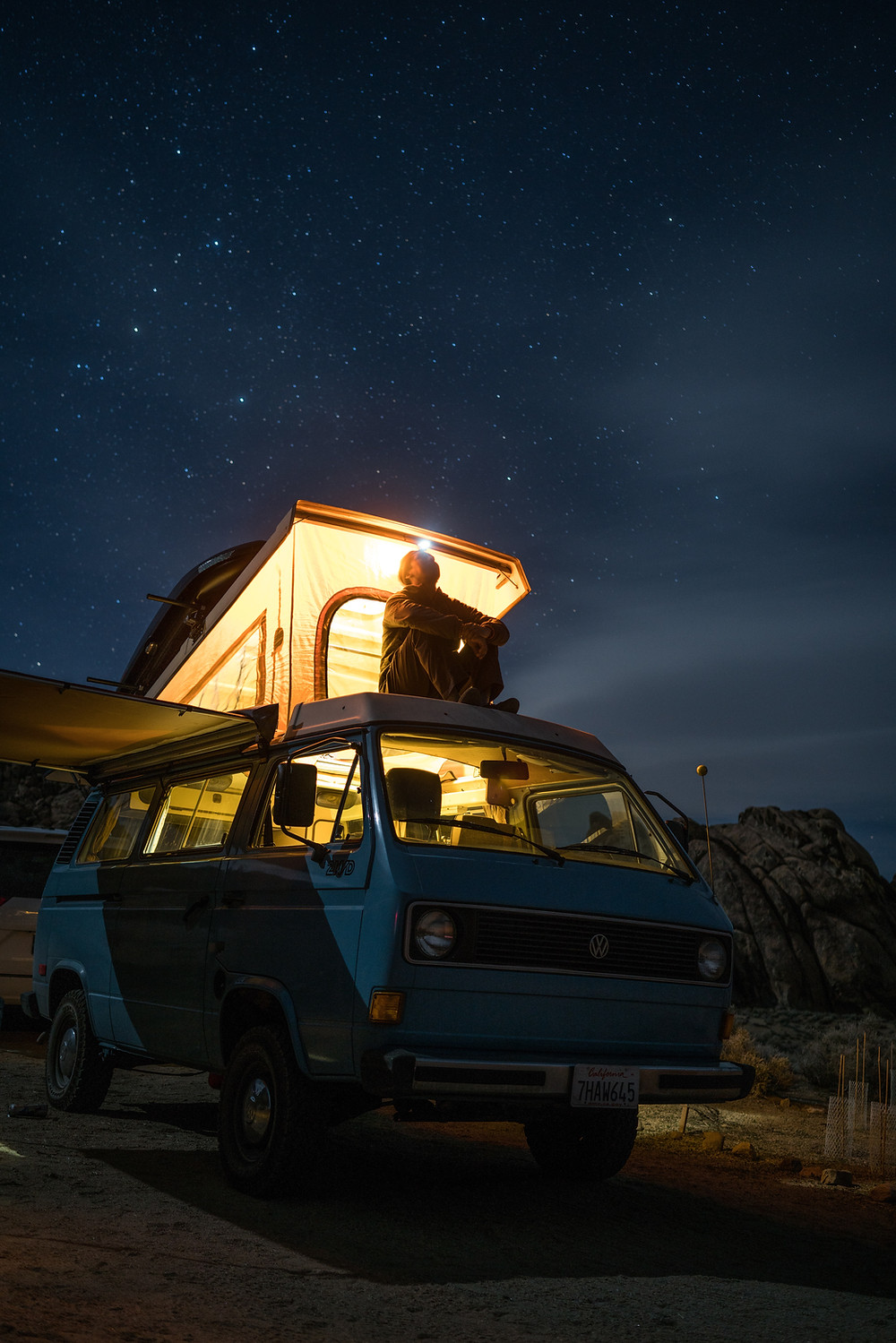 Man sitting on top of an overlanding vehicle equipped with mounted roof tent under starry and clear night sky