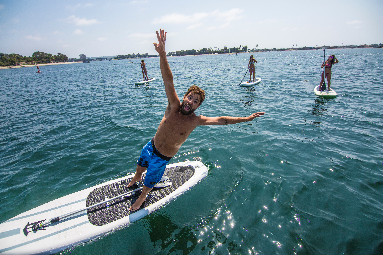 man jumping off SUP board