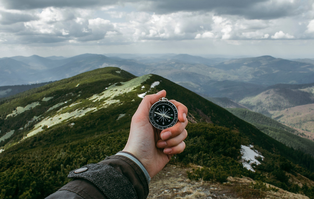Compass on mountain top represents advice of Pleasanton estate planning attorney to review IRA trusts and beneficiaries.
