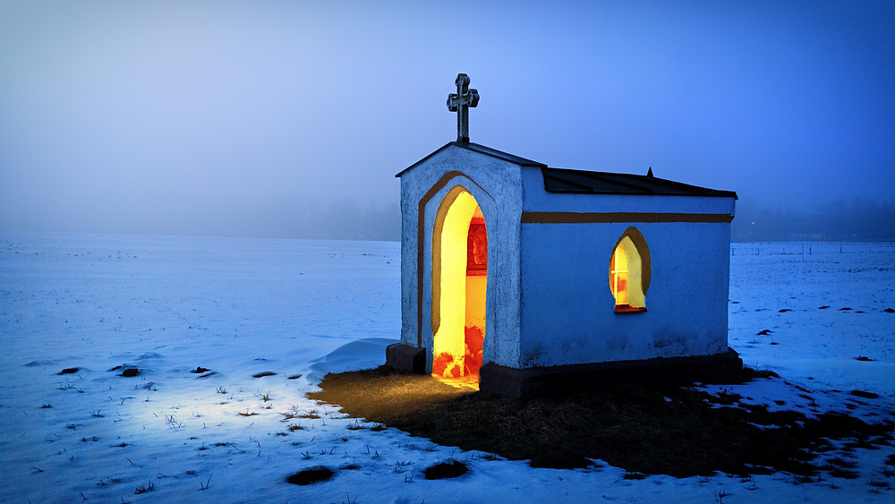 Light shining out from the doorway of a small church at night.