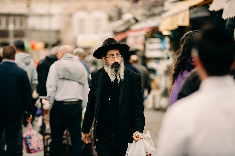 Older Jewish man with a black hat, white beard, black suit walking down the street