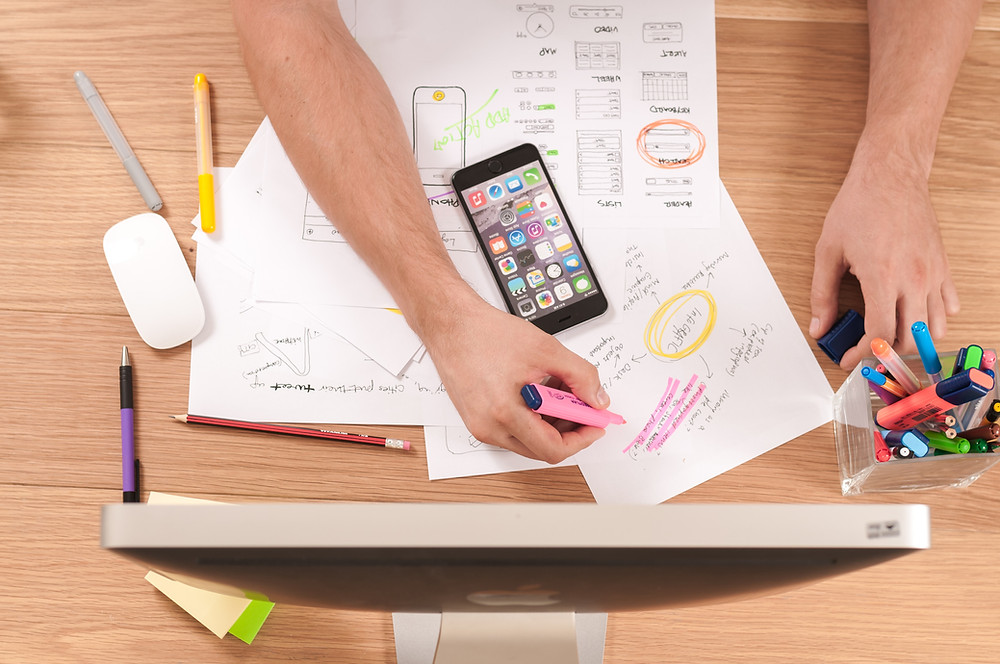 Pessoa riscando papel com marca texto com celular, tela de computador e porta canetas próximo