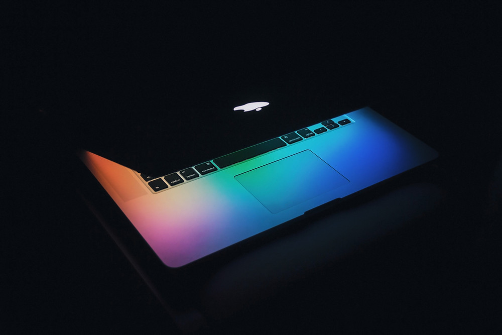 Apple macbook with screen glowing in dark