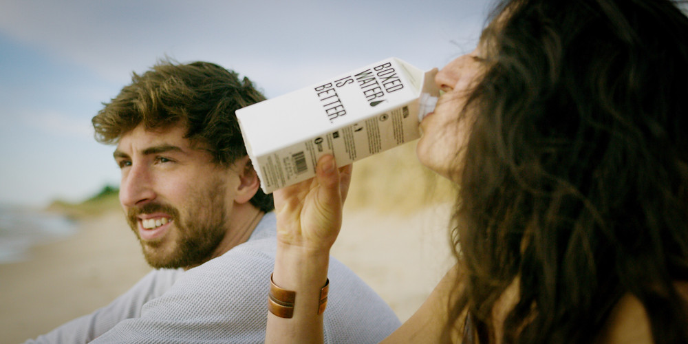 """Woman drinking water from carton that reads """"Boxed Water Is Better."""" sitting next to man staring off into the distance."""