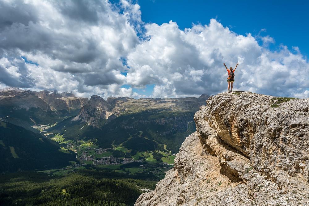 mężczyzna w górach wznosi ręce ku niebu