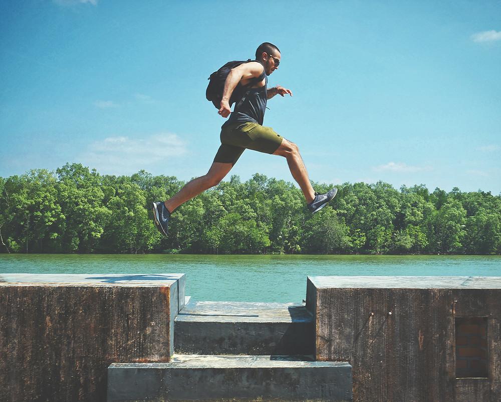 Mann springt über eine Lücke, Wasser und Wald im Hintergrund