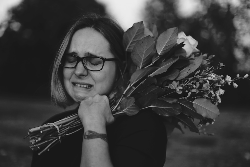 Woman holding bouquet of roses and crying.