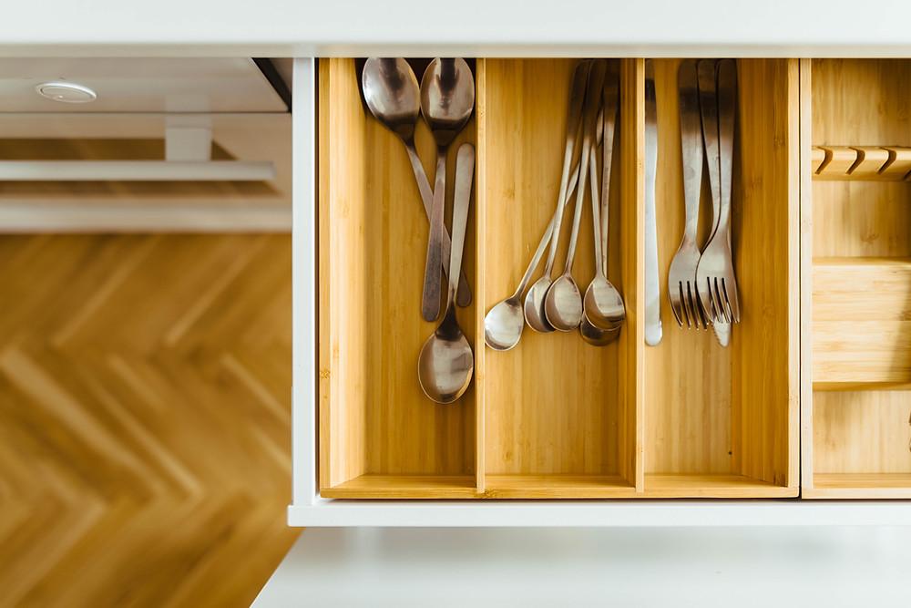Silverware stored inside wooden trays inside drawer