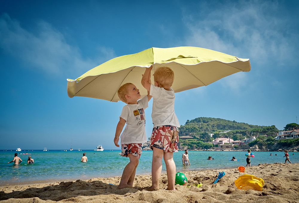 Two little boys with blonde hair and red shorts putting up a big yellow umbrella at the beach while people swim in the ocean