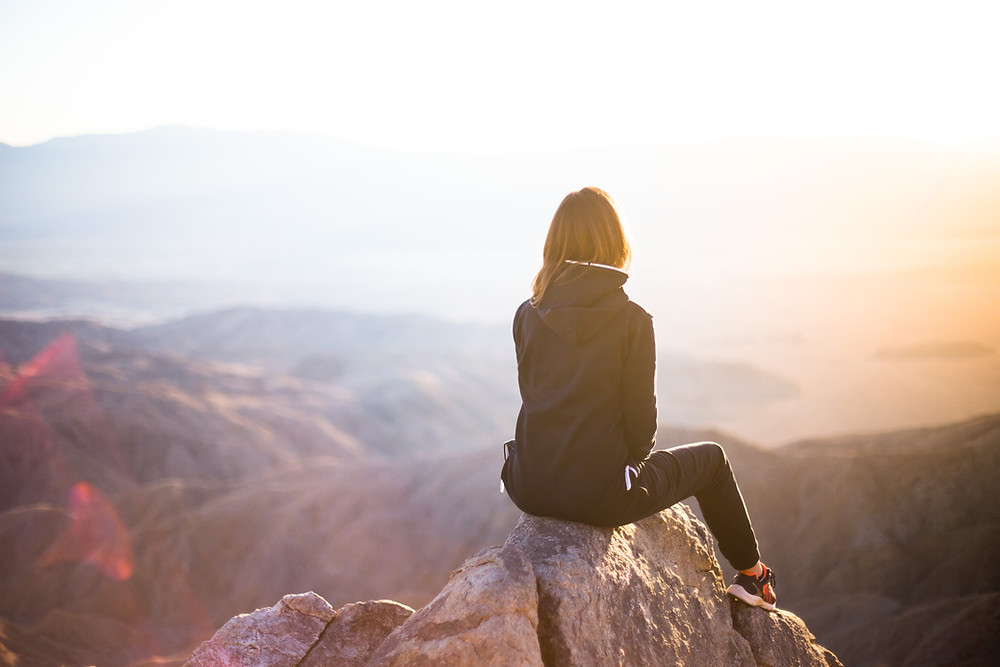 woman sitting on a mountaintop contemplating her answers to life's two most important questions