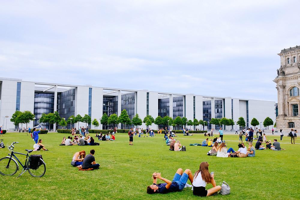 אנשים יושבים על הדשא מול הרייכסטאג