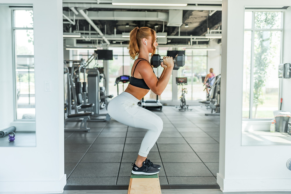 girl doing squat with dumbells at gym