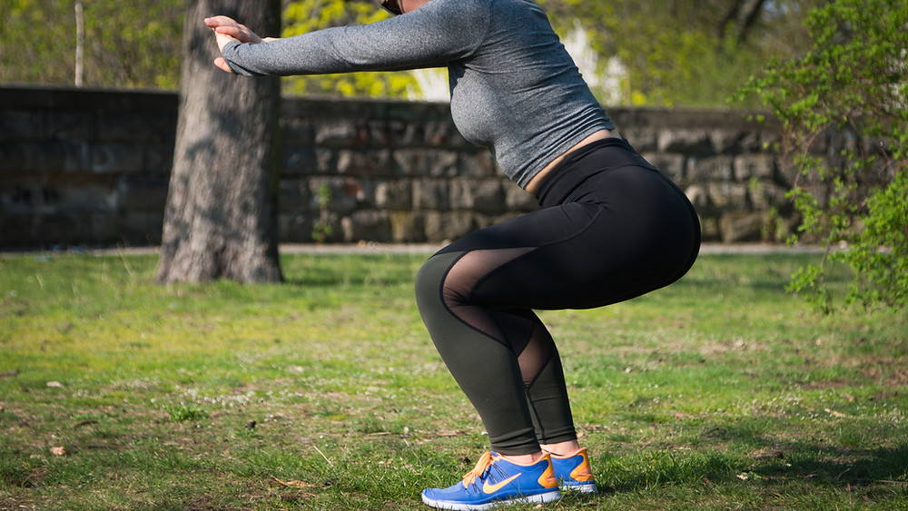 Woman doing squats and stretching legs outside