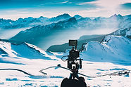 camera filming mountains filled with snow