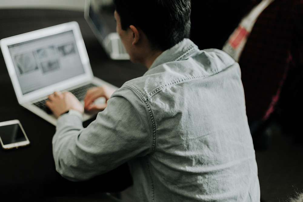 Singaporean student researching on his laptop in a cafe