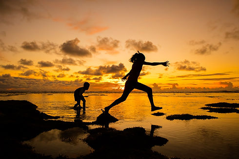 Children playing by the ocean, one skipping from rock to rock