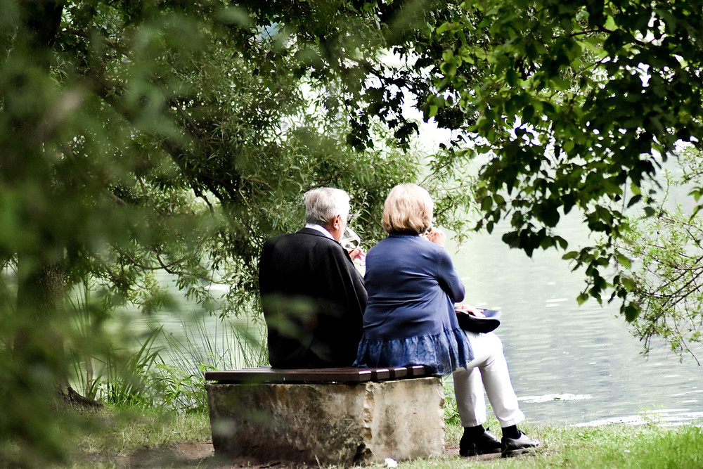 A elderly couple seated on a bench by a river, sipping wine.