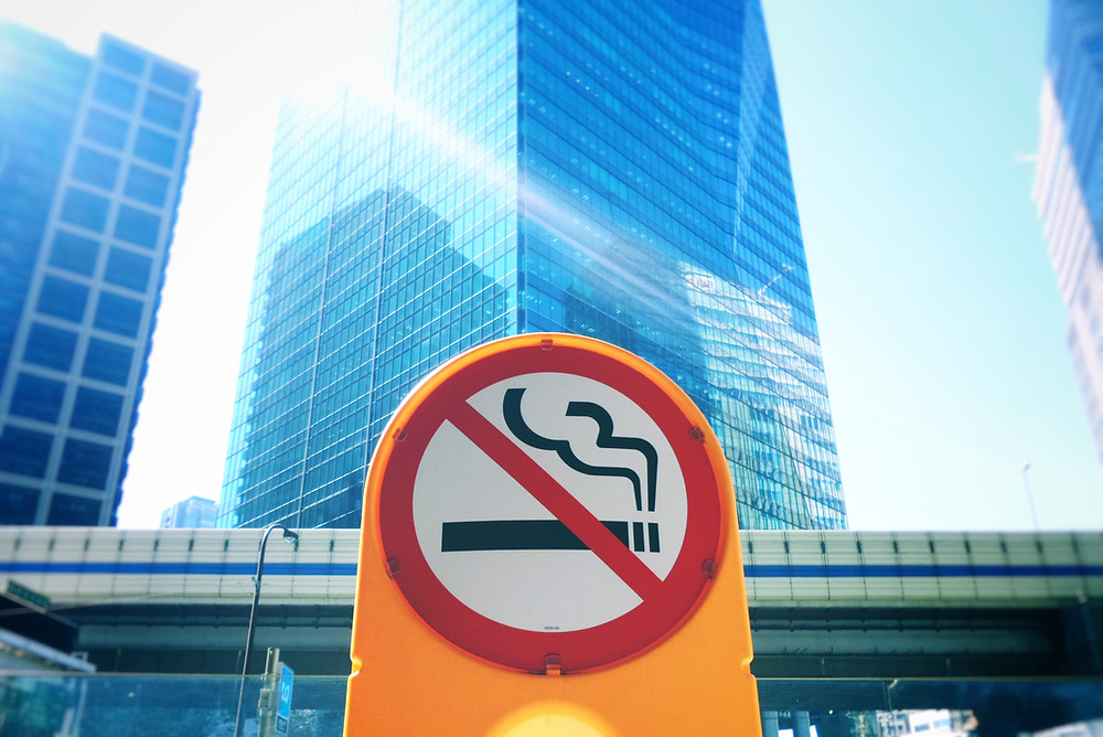 a red no smoking sign on a yellow plastic bollard, in the background there is a large skyscraper and other tall buildings and a bridge for trains