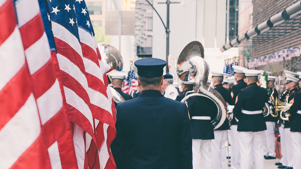 Service member stands next to American flags behind a marching band in a city.