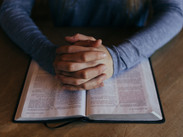 Man praying with hands clasped on an open bible