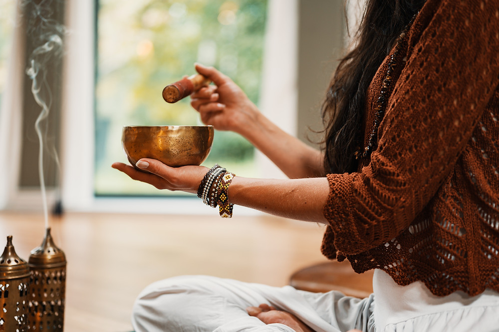 woman with inscents burning ringing a meditation bowl