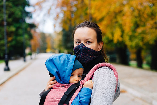 Woman in mask holding child