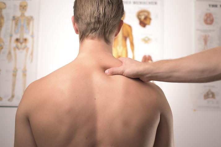 Homem de costas recebendo um tratamento, da fisioterapia traumato-ortopédica