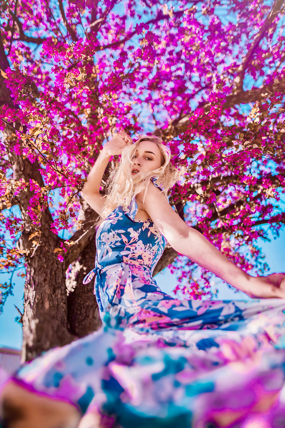 Woman with long blonde hair in a blue and magenta sleeveless dress posing in front of a tree with purple flowers.
