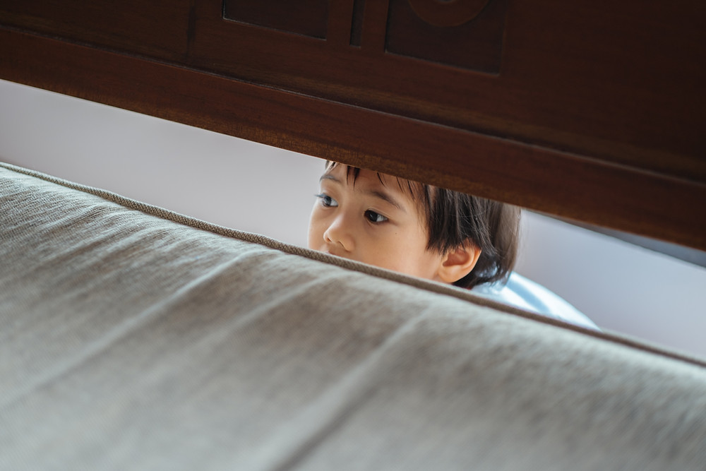 Little kid hiding behind the bed and peeking out.