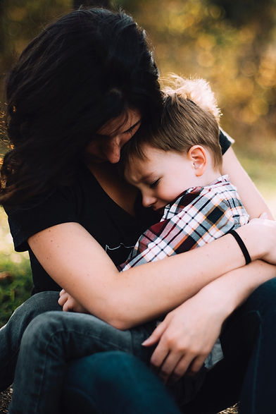 Grieving mother holding young son