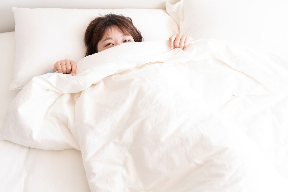 asian woman in bed with cozy white blanket insomnia neurobiology