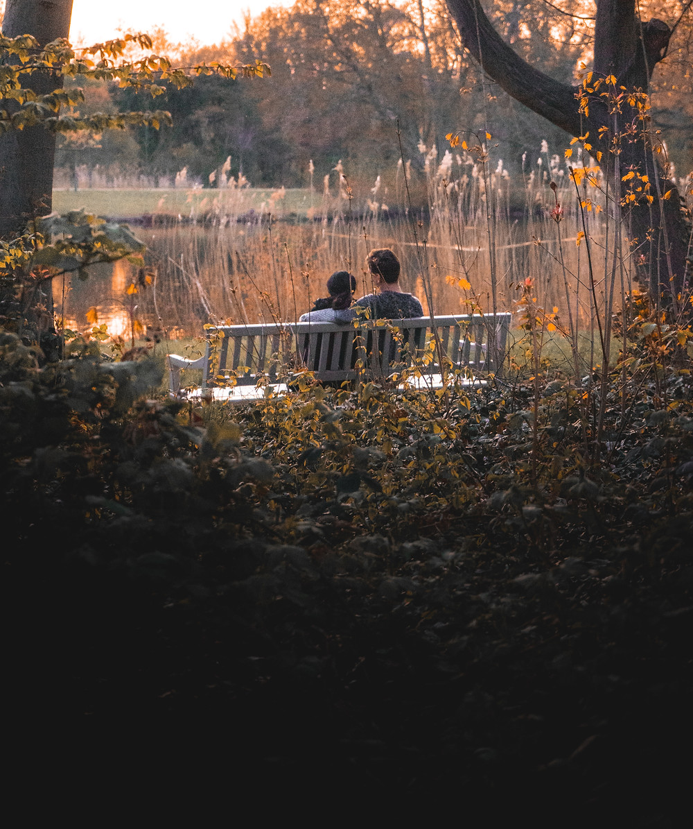 A couple sits closely on a park bench overlooking a pond in the Fall season.