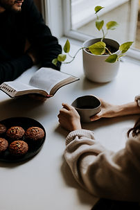 Image by Priscilla Du Preez two people sitting at a white large table, one is holding a cup, the other is holding a book, a plant in a white plant pot is on the table next to a black plate with chocolate muffins