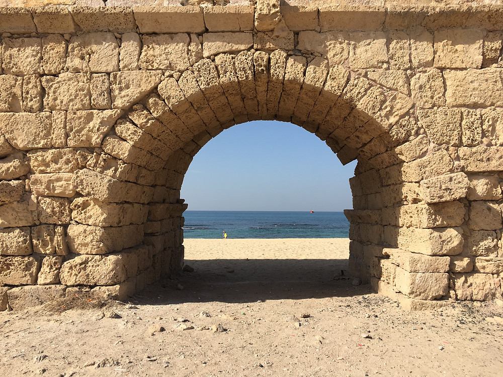 A arch of the Caesarea Aqueduct with a view of the sea