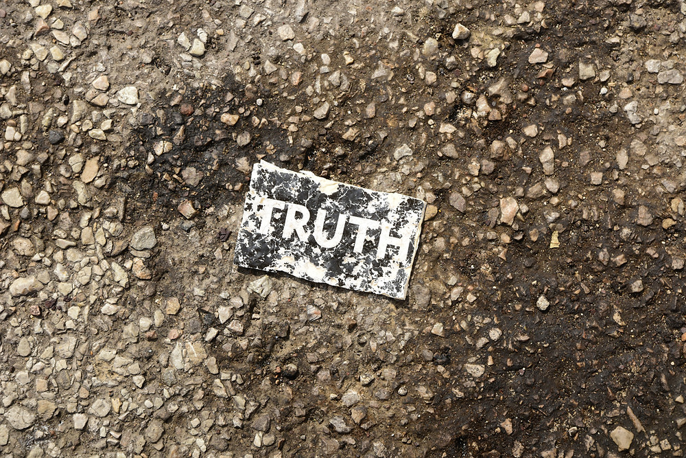 Paper with the word truth laying in the dirt.