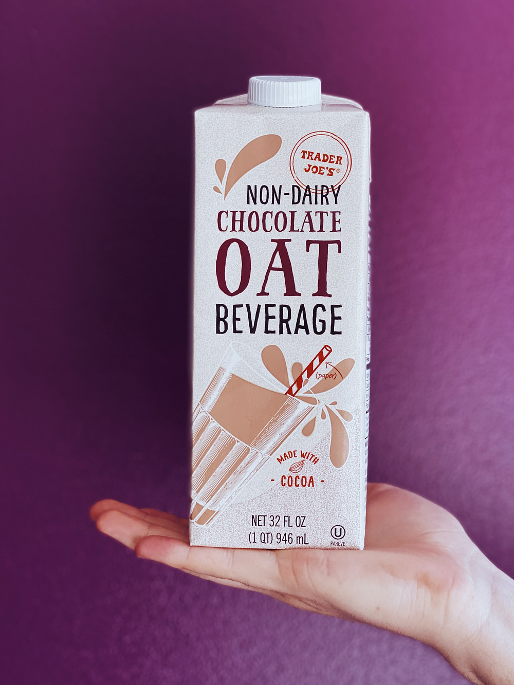 photo shows someone holding up a carton of chocolate non dairy oat milk