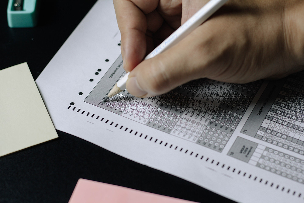 A Student Takes a Standardized Test / SAT and is filling in bubbles on the exam with a white pencil