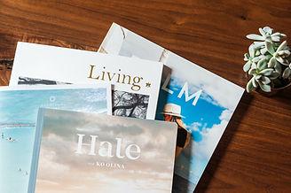 corner of 4 magazines spread on wood table