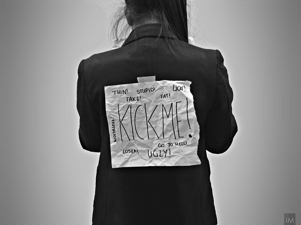 "woman wearing a ""kick me"" sign on back due to bullies"