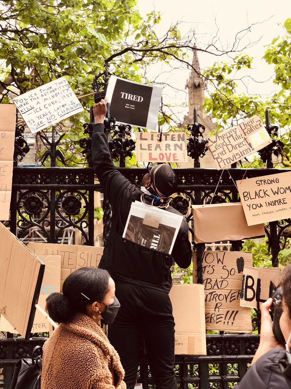Image of Black Lives Matter protesters standing in front of a gate covered by placards