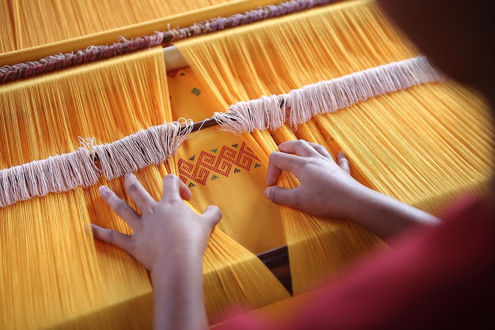 A man weaving yellow fabric on a handloom