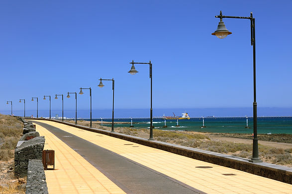 seaside-sidewalk-promenade-with-raw-of-street-lights-on-black-composite-poles-overlooking-beach-with-city-in-the-background