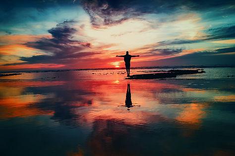 Image by Mohamed Nohassi henkilö seisoo veden ympäröimänä pienellä saarella auringonlaskussa.